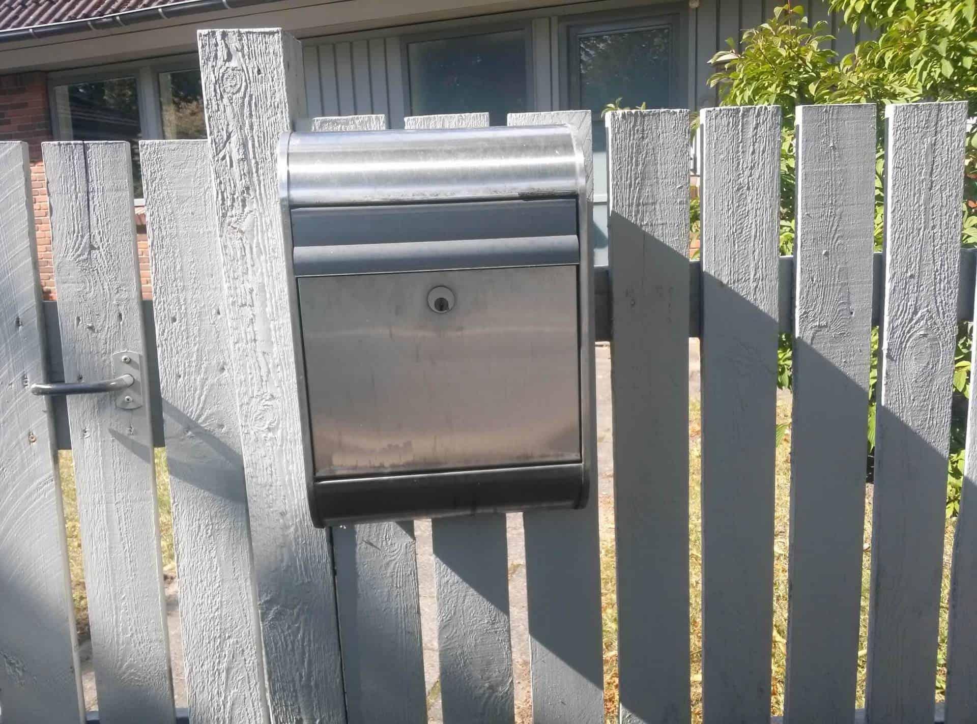 Grå postkasse på stakit